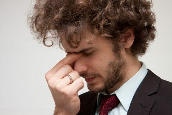 仕事中に眠気を感じて困っている男性のイメージ
