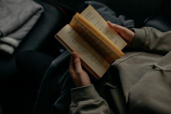 カラダの勉強会で肩こりの原因についての本を読んでいるイメージ