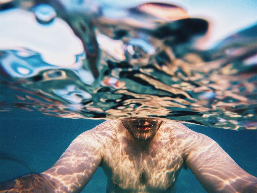 貧血は酸欠であることを説明するための水の中で酸素がない状態で泳いでいる男性のイメージ