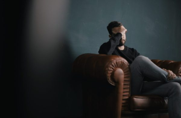 筋トレが原因で眠れなくなって頭痛で悩んでいる男性のイメージ